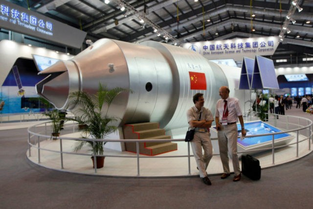 In this Nov. 16, 2010 file photo, visitors sit beside a model of China's Tiangong-1 space station at the 8th China International Aviation and Aerospace Exhibition in Zhuhai in southern China's Guangdong Province. China's defunct Tiangong 1 space station is expected to re-enter Earth's atmosphere within the next day. The …