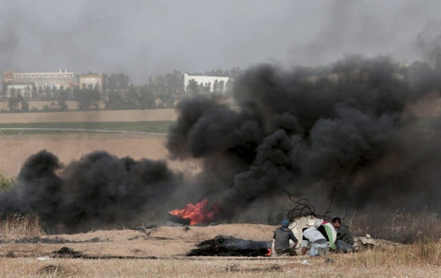 The Latest: Gazans burn tires, Israeli troops open fire