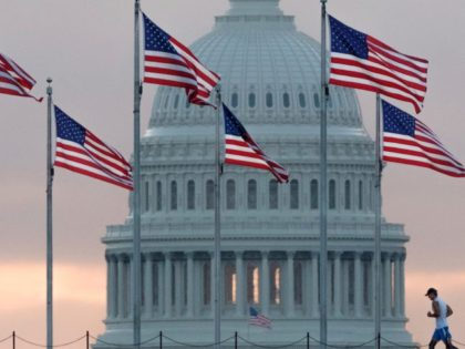 In this Sept. 27, 2017, file photo, a early morning runner crosses in front of the U.S. Capitol as he passes the flags circling the Washington Monument in Washington. Congress returns from spring break Monday, April 9, 2018, scrambling to compile a to-do list that will satisfy a president they …