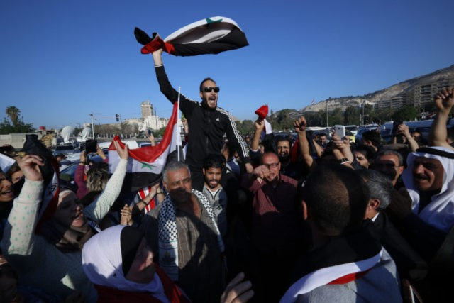 Syrians gather in capital in defiance after airstrikes