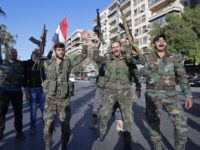 Syrian soldiers hold their weapons as they dance and chant slogans against U.S. President Trump during demonstrations following a wave of U.S., British and French military strikes to punish President Bashar Assad for suspected chemical attack against civilians, in Damascus, Syria, Saturday, April 14, 2018. Hundreds of Syrians are demonstrating …