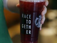 "In this March 18, 2015, file photo, a Starbucks barista holds an iced tea drink with a ""Race Together"" sticker on it at a Starbucks store in Seattle. Three years ago, Starbucks was widely ridiculed for trying to start a national conversation on race relations by asking its employees to …"