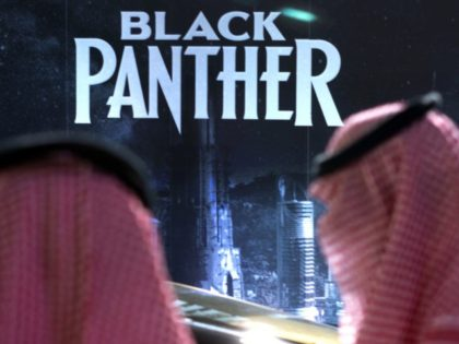 "Visitors wait in front of a ""Black Panther"" movie banner, during an invitation-only screening, at the King Abdullah Financial District Theater, in Riyadh, Saudi Arabia, Wednesday, April 18, 2018. Saudi Arabia held a private screening of the Hollywood blockbuster ""Black Panther"" Wednesday, to herald the launch of movie theaters that …"