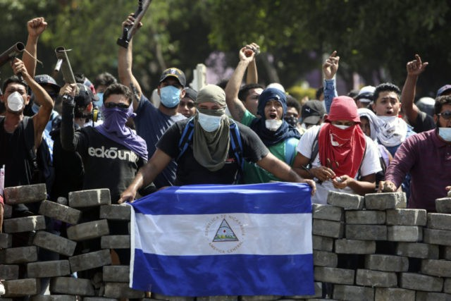 Masked protesters, one with a Nicaraguan flag, yell from the road block they erected as they face off with security forces near the University Politecnica de Nicaragua (UPOLI) in Managua, Nicaragua, Saturday, April 21, 2018. Nicaragua's government said on Saturday it is willing to negotiate over controversial social security reforms …