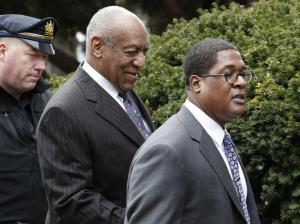 Topless protester charges Bill Cosby as assault retrial begins