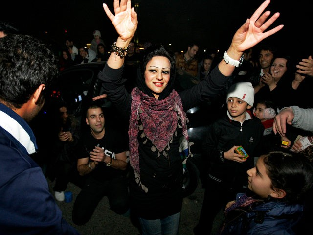 Between the people, a woman dances, in the Pardisan Park in Tehran, Iran, Tuesday, March 13, 2012, during Chaharshanbe Souri, or Wednesday Feast, an ancient Festival of Fire, on the eve of the last Wednesday of the year. Iranians jump over burning bonfires while throwing firecrackers, celebrate arrival of the …