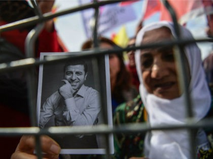 A woman standing behind a fence holds a portrait of Selahattin Demirtas, a jailed former leader of the Peoples' Democratic Party HDP, as Turkish Kurds gather during the celebration of Nowruz (aka Noruz or Newroz), the Persian calendar New Year, in Istanbul on March 21, 2018. / AFP PHOTO / …