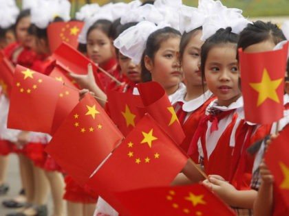 Young Vietnamese girls wave Chinese and Vietnamese flags as visiting Chinese vice president Xi Jinping (not pictured) is greeted during the official welcoming ceremony at the presidential palace in Hanoi on December 21, 2011. Xi is on a three-day official visit for talks with all top Vietnamese leaders on a …