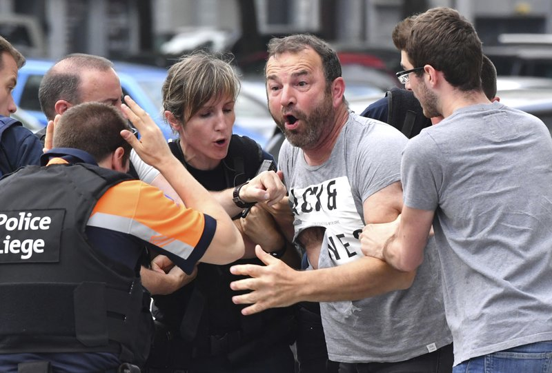Police try to calm a man who crossed over a police line at the scene of a shooting in Liege, Belgium, Tuesday, May 29, 2018. A gunman killed three people, including two police officers, in the Belgian city of Liege on Tuesday, a city official said. Police later killed the attacker, and other officers were wounded in the shooting. (AP Photo/Geert Vanden Wijngaert)