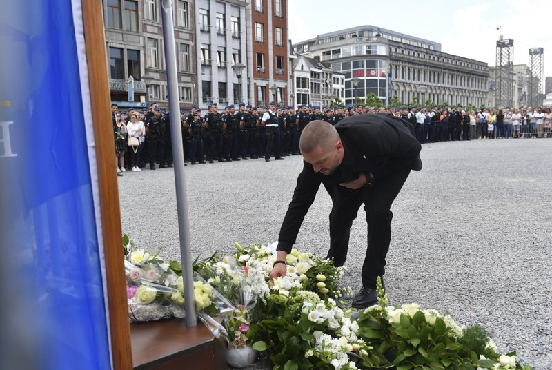A man leaves flowers at a memorial as he attends a moment of silence for shooting victims near the City Hall in Liege, Belgium, Wednesday, May 30, 2018. A gunman killed three people, including two police officers, in the Belgian city of Liege on Tuesday. Police later killed the attacker, and other officers were wounded in the shooting.(AP Photo/Geert Vanden Wijngaert)