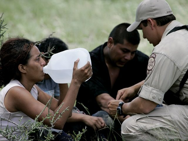 Border Patrol agent Isaac David, right, talks with illegal immigrants stopped on a ranch near Falfurrias, Texas, Wednesday, July 5, 2006. David is part of the Border Patrol's Search, Trauma and Rescue team, known as Borstar, he is part of an elite force that can track someone with a faxed …