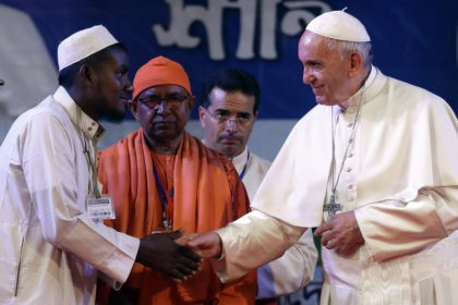 Pope Francis, right, shakes hands with a Rohingya Muslim refugee during an interfaith and ecumenical meeting for peace in the garden of the archbishop's residence, in Dhaka, Bangladesh, Friday, Dec. 1, 2017. (AP Photo/Andrew Medichini)
