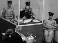 Nazi war criminal Adolph Eichmann stands in a protective glass booth flanked by Israeli police during his trial June 22, 1961 in Jerusalem. The Israeli police donated Eichmann's original handprints, fingerprints and mugshot to Jerusalem's Yad Vashem Holocaust memorial ahead of Israel's annual Holocaust remembrance day May 4, 2005 which …