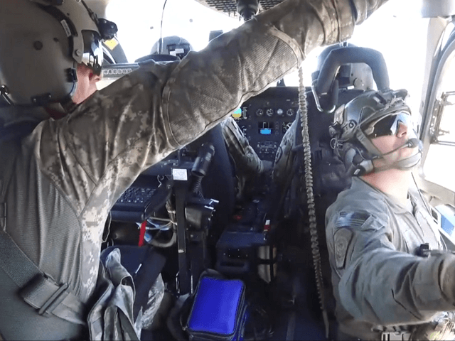 Chief Warrant Officer Weston Holtmeyer (front left), Chief Warrant Officer Andrew Ottinger (front right) and Sergeant Brent Woods (left rear) of the Missouri National Guard, along with BPA Zachary Pruett (left rear) of Tucson Sector's Mobile Response Team, conduct aerial surveillance near Tucson, AZ as part of the first operational …