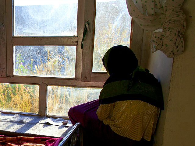 BAMIYAN, AFGHANISTAN - OCTOBER 8: Rahima (L), 18, looks out the window of her room with another battered woman at a women's shelter October 8, 2010 in Bamiyan, Afghanistan. Rahima, from Maydan Wardak, was a child bride, forced to marry at age 11. Until women's shelters were started, something that …