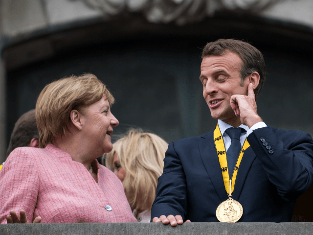 German Chancellor Angela Merkel (L-R) and French President Emmanuel Macron gesture on the balcony of the town hall of Aachen after Macron recieved the International Charlemagne Prize at a ceremony on May 10, 2018 in Aachen, Germany.