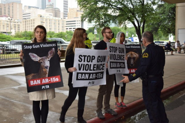 A Dallas police officer speaks to the four anti-gun protesters outside the NRA Annual Meeting in Dallas on Friday. (Photo: Bob Price/Breitbart Texas)