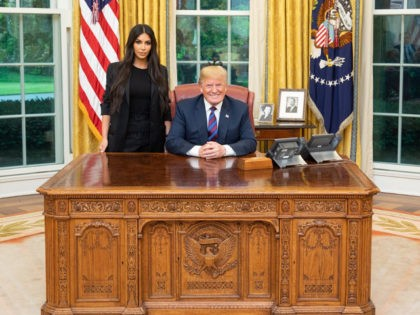 Donald Trump and Kim Kardashian in the White House. Both are behind the Oval Office's Resolute Desk.