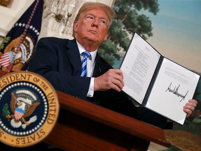 WASHINGTON, DC - MAY 08: U.S. President Donald Trump holds up a memorandum that reinstates sanctions on Iran after he announced his decision to withdraw the United States from the 2015 Iran nuclear deal in the Diplomatic Room at the White House May 8, 2018 in Washington, DC. After two …