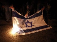 Illustrative photo of protesters burning an Israeli flag during a protest against Israel's attacks of the Gaza Strip. (AP/Kostas Tsironis)