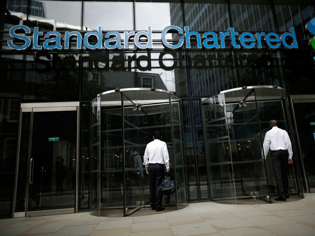 LONDON, ENGLAND - AUGUST 07: People enter the Standard Chartered bank's offices on August 7, 2012 in London, England. Standard and Chartered has been accused by American financial investigators of making billions of pounds worth of transactions with the Iranian regime, despite strict economic sanctions being in place. (Photo by …