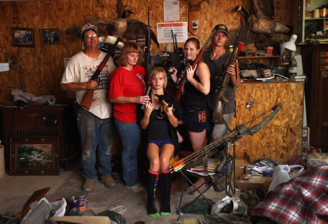 LOGAN, KS - AUGUST 24: The Becker family, including Darren, his wife Dorthy and their children Renee 15, Katie, 17 and Charlie, 19, show off a small part of the family weapons collection, and their pet Mini Chihuahua, at the Becker farm August 24, 2012 in Logan, Kansas.
