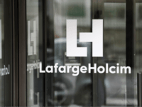 A picture taken on March 9, 2017, in Paris, shows a logo at an entrance of the French headquarters of LafargeHolcim, a group created in 2015 by the merger of French cement manufacturer Lafarge and its Swiss counterpart Holcim. French-Swiss group LafargeHolcim is ready to sell its cement to build …