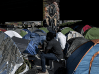 TOPSHOT - Migrants sit by tents at a makeshift camp set under a bridge near Porte de la Villette, northern Paris on April 20, 2018. (Photo by CHRISTOPHE ARCHAMBAULT / AFP) (Photo credit should read CHRISTOPHE ARCHAMBAULT/AFP/Getty Images)