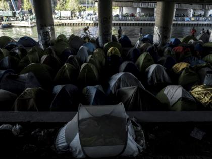 Migrants stand by tents at a makeshift camp set under a bridge near Porte de la Villette, northern Paris on April 20, 2018. (Photo by CHRISTOPHE ARCHAMBAULT / AFP) (Photo credit should read CHRISTOPHE ARCHAMBAULT/AFP/Getty Images)