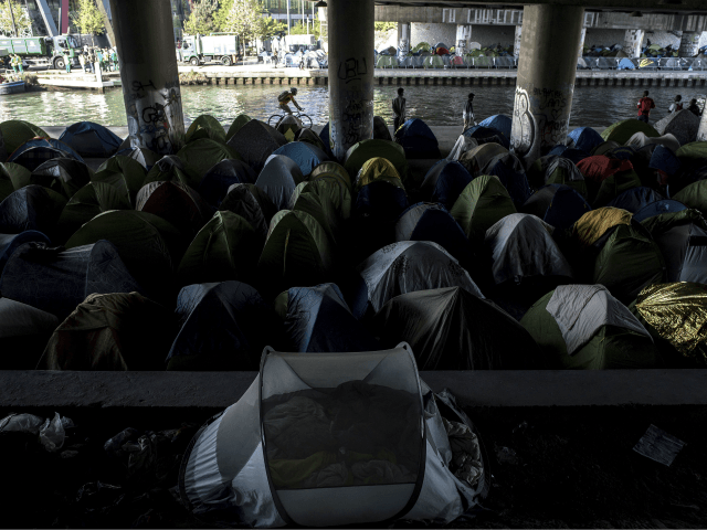 Migrants stand by tents at a makeshift camp set under a bridge near Porte de la Villette, northern Paris on April 20, 2018. (Photo by CHRISTOPHE ARCHAMBAULT / AFP) (Photo credit should read CHRISTOPHE ARCHAMBAULT/AFP/Getty Images)