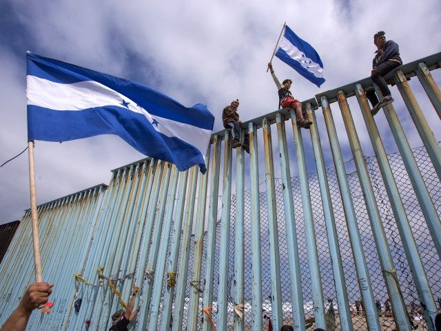 """Caravan Migrants"" climb border fence between Tijuana and San Diego. (File Photo: David McNew/Getty Images)"