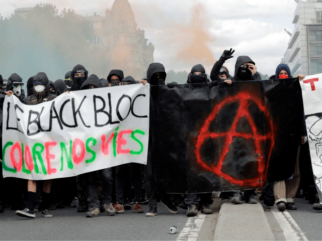Protestors chant slogans as they march behind banners during a demonstration on the sidelines of a march for the annual May Day workers' rally in Paris on May 1, 2018. (Photo by Thomas SAMSON / AFP) (Photo credit should read THOMAS SAMSON/AFP/Getty Images)