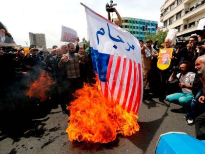 Iranian protesters burn a US flag as they hold anti-US placards and shout slogans during a demonstration after Friday prayer in the capital Tehran on May 11, 2018. - Iran's foreign minister will embark on a diplomatic tour to try to salvage the nuclear deal amid high tensions following the …