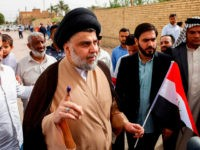 Iraqi Shiite cleric and leader Moqtada al-Sadr (C-L) shows his ink-stained index finger and holds a national flag while surrounded by people outside a polling station in the central holy city of Najaf on May 12, 2018 as the country votes in the first parliamentary election since declaring victory over …