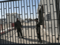 Palestinian security forces loyal to the Palestinian Authority (L) stand at the gate of the Kerem Shalom crossing, the main passage point for goods entering Gaza, after is was closed by Israel following the discovery of tunnels underneath the crossing, in the southern Gaza Strip town of Rafat on January …