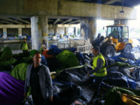 Paris town hall workers clear a migrant makeshift camp, in Paris, Wednesday, May 30, 2018. The mainly African migrants were being moved out of their tent camp along a canal used by joggers and cyclists on the city's northeast edge, put in buses and taken to gymnasiums in the Paris …