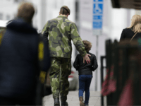 A soldier and a boy walk away after they offered flowers near the department store Ahlens following a suspected terror attack in central Stockholm, Sweden, Saturday, April 8, 2017.