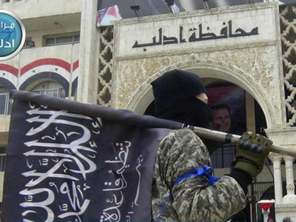 FILE - In this file photo posted on the Twitter page of Syria's al-Qaida-linked Nusra Front on March 28, 2015, which is consistent with AP reporting, a fighter from Syria's al-Qaida-linked Nusra Front holds his group flag as he stands in front of the governor building in Idlib province, north …