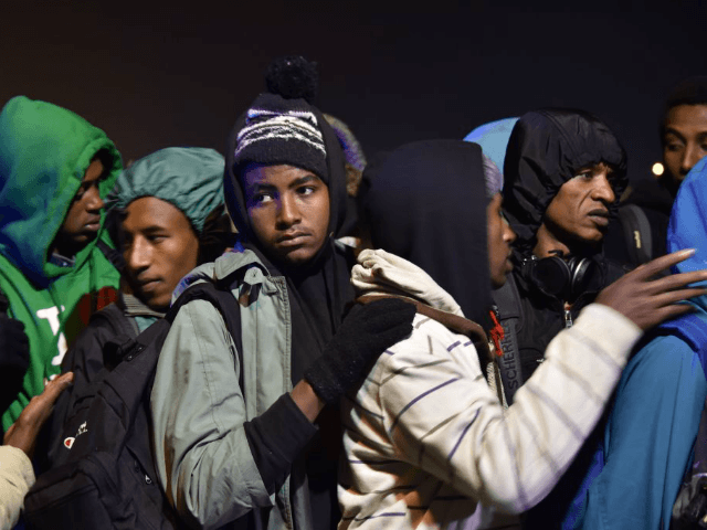 Migrants queue for transportation by bus to reception centres across France, from the 'Jungle' migrant camp in Calais, northern France, on October 24, 2016.