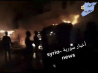 This frame grab from video provided on Wednesday, May, 9, 2018 by Syria News, shows people standing in front of flames rising after an attack on an area known to have numerous Syrian army military bases, in Kisweh, south of Damascus, Syria on Tuesday. The Britain-based Syrian Observatory for Human …