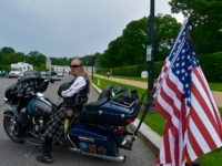 A biker wearing a kilt with three American flags on his Harley Davidson arrives at Arlington National Cemetery on Sunday. (Penny Starr/Breitbart News)