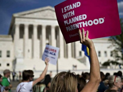 A demonstrator opposed to the Senate Republican health-care holds a sign that reads 'I Stand With Planned Parenthood' while marching near the U.S. Supreme Court in Washington, D.C., U.S., on Wednesday, June 28, 2017. Several Senate Republicans began to question today whether their health-care bill should repeal a tax on …