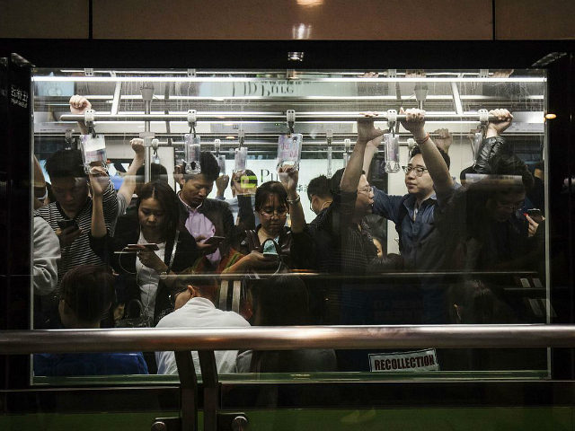 Passengers use smartphones while riding on a subway train in Shanghai, China, on Friday, Oct. 13, 2017. A number of economic indicators show 'stabilized and stronger growth' and the momentum of a 6.9 percent expansion in the first six months of 2017 'may continue in the second half,' Peoples Bank of China …