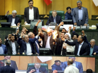 Iranian lawmakers burn two pieces of papers representing the U.S. flag and the nuclear deal as they chant slogans against the U.S. at the parliament in Tehran, Iran, Wednesday, May 9, 2018. Iranian lawmakers have set a paper U.S. flag ablaze at parliament after President Donald Trump's nuclear deal pullout, …