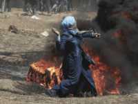 A Palestinian woman hurls stones towards Israeli troops during a protest at the Gaza Strip's border with Israel, Monday, May 14, 2018. Israeli fire has killed dozens of Palestinians during mass protests along the Gaza border, marking the deadliest day of violence since a devastating 2014 cross-border war and casting …