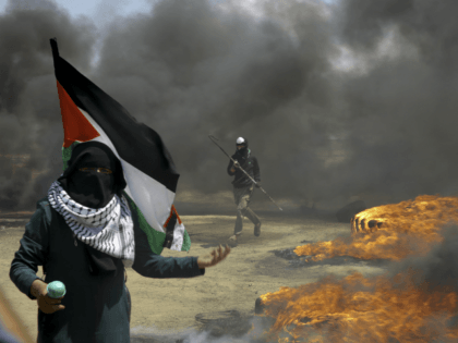 A woman holds a Palestinian flag as a protester burns tires near the Israeli border fence, east of Khan Younis, in the Gaza Strip, Monday, May 14, 2018. Thousands of Palestinians are protesting near Gaza's border with Israel, as Israel prepared for the festive inauguration of a new U.S. Embassy …