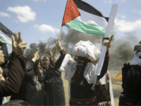 Palestinian women wave national flags and chant slogans near the Israeli border fence, east of Khan Younis, in the Gaza Strip, Monday, May 14, 2018. Thousands of Palestinians are protesting near Gaza's border with Israel, as Israel prepared for the festive inauguration of a new U.S. Embassy in contested Jerusalem. …