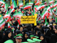 Iranian schoolgirls wave their national flag and hold an anti-US slogan during celebrations in Tehran's Azadi Square (Freedom Square) to mark the 37th anniversary of the Islamic revolution on February 11, 2016. / AFP / ATTA KENARE (Photo credit should read ATTA KENARE/AFP/Getty Images)