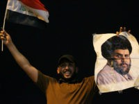 An Iraqi man celebrates with a picture of Shiite cleric Muqtada Sadr during the general election in Baghdad on May 14, 2018. - The race to become Iraq's next prime minister appeared wide open as two outsider alliances looked to be in the lead after the first elections since the …
