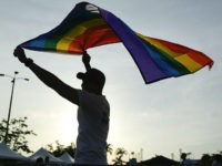A man holds up a rainbow flag at the end of the annual Gay Pride parade in Panama City, Saturday, July, 1, 2017. . (AP Photo/Arnulfo Franco)